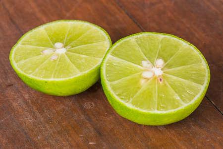 half cut: half cut lime on brown wood table.