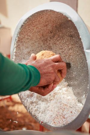 hand take coconut to machine to make coconut milk photo