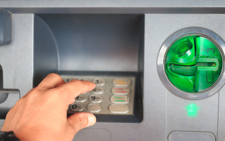 ATM close-up with male hand photo
