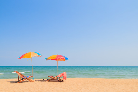 Strandstoel en paraplu op zand strand