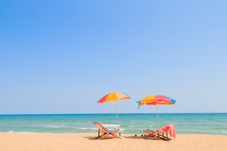 strandstoel: Strandstoel en paraplu op zand strand