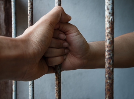 political prisoner: woman and man hands of jail holding prison bars Stock Photo