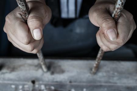 rejas de hierro: manos de la cárcel sosteniendo barras de la prisión Foto de archivo