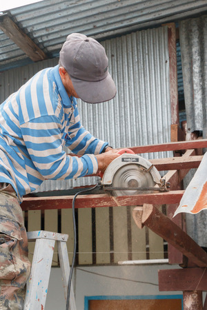 tar paper: CHUMPON THAILAND  SEPTEMBER 9 2014 : The carpenter repairing the old roof in the morning on September 9 2014 at Chumpon Prachuap keereekhun Thailand. Editorial