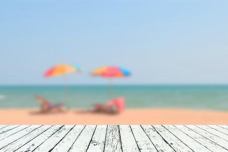 Afbeelding van wazig zee blauwe hemel en kleurrijke paraplu met houten plank onder het