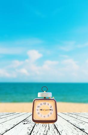 Zomertijd, Uitstekende klok gezet op houten Wazig beeld van vreedzame zee achtergrond. Stockfoto