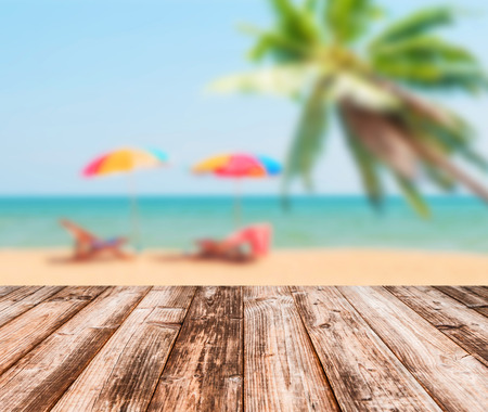 Image of blurred sea blue-sky and colorful umbrella with coconut wooden plank under image