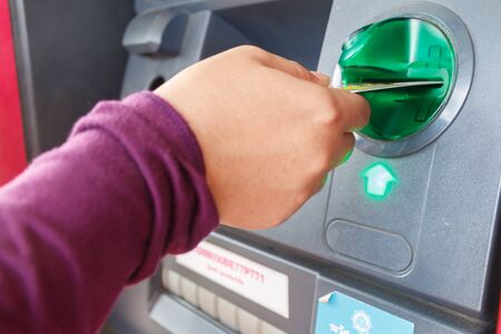 personal safety: ATM close-up with woman hand Stock Photo