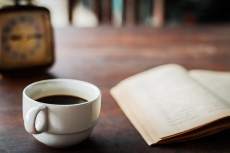 blown: Cup of coffee with book and clock set on morning on blown background
