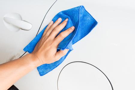 Close-up mannelijke hand met blauwe microfiber doek schoonmaken van de auto