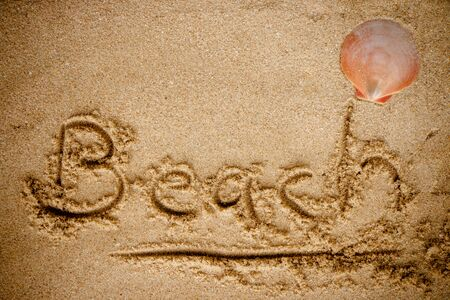 sand writing: Word Beach writing on sand beach background. Stock Photo