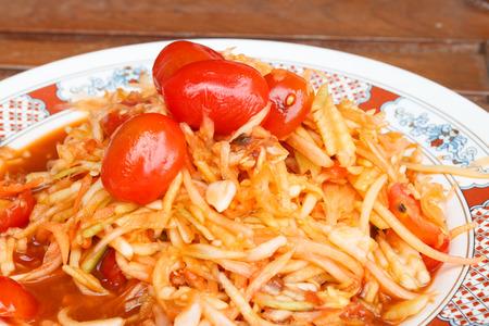 unripened: Papaya salad with tomatoes thai style food with wood background