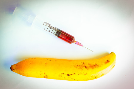 genetic food modification: banana with a syringe on a white background Stock Photo