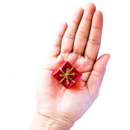 bonbonniere: Human hand holding small red gift box on white background Stock Photo