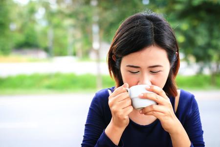 mujer tomando cafe: Sonrisa asiática sosteniendo la taza de café mujer con el fondo de la naturaleza. Foto de archivo
