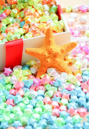 paper fold: colorful of paper fold christmas stars spilling out from the paper box to wood surface Stock Photo