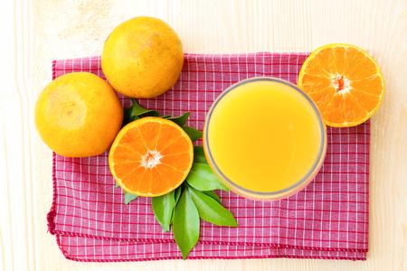 Glass of orange juice with orange slice on soft wooden background Stock Photo