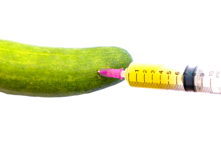 ehec: syringe with cucumber on white background