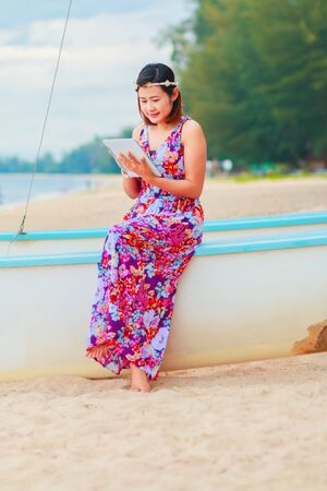 colorful dress: Smiling women using tablet computer with colorful dress sitting at the beach