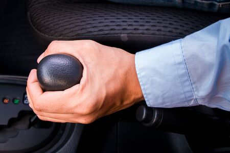 gearstick: business man holding gear in car. Stock Photo