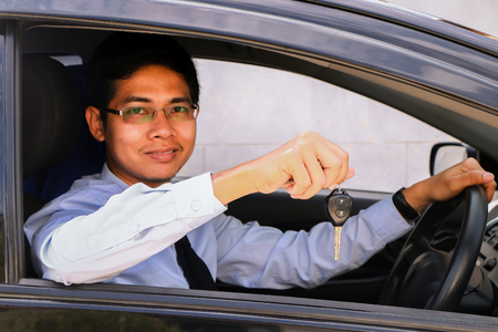 auto leasing: Business man smiling showing key and sit in car
