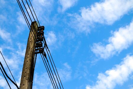 disordered: Electricity post with overgrown wire on sky background. Stock Photo