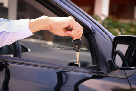 auto leasing: Business man giving car key, focus on key.