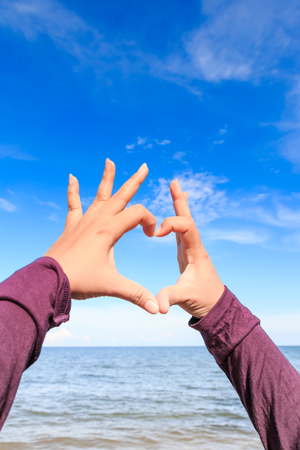 handsign: heart, hand, shape, sky, sign, beach, blue, sea, closeup, handsign, natural, tropical, day, concept, holiday, symbol, horizon, finger, celebration, summer, people, paradise, love, abstract, icon, connection, relationship, emotion, healthy, young, woman, g