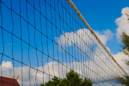 detain: Wire mesh fence against blue sky Stock Photo