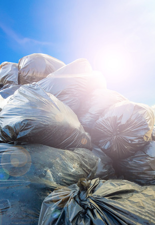 flare stack: Dirty garbage bags with flare on sky background Stock Photo
