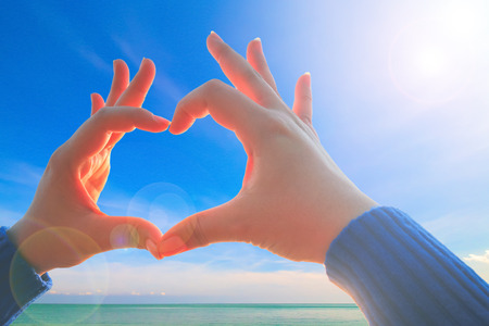 valentine s day beach: woman hand making love sign on the nature, nature background, Love nature concept, love to travel at nature, love nature symbol, mountain at nature. Stock Photo