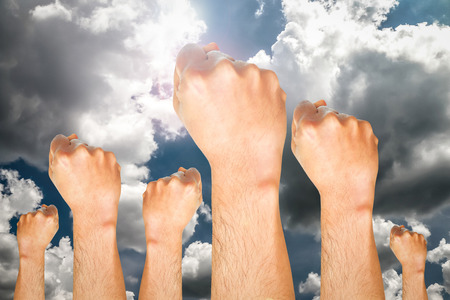 air demonstration: group of human hand showing fist on sky background with the sun, fighting fist concept, fist sign, fist symbol. Stock Photo