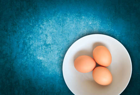 wooden insert: eggs on old blue wooden, raw eggs, three eggs, egg on blank space for insert your text or products. Stock Photo