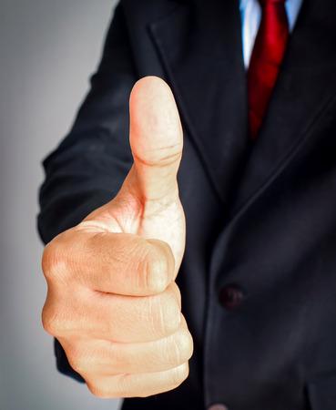 gesturing: Businessman showing gesturing Thumbs up.