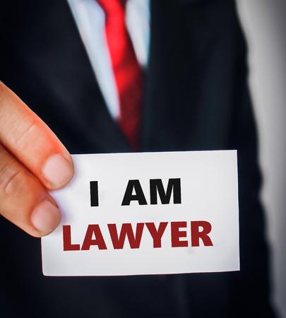 denunciation: businessman in black suit holding sign I AM LAWYER