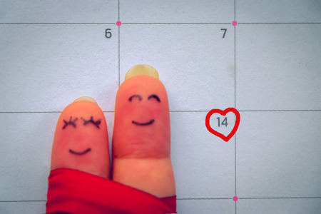 number 14: Abstract vintage tone of finger writing face of man and woman holding together smiling on calendar and marking on number 14 with love sign, valentine concept. Stock Photo