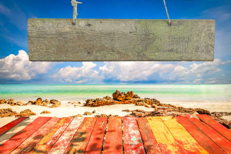 wooden insert: Beautiful sky with sea on the peaceful beach for relax with blank wooden signboard for insert text