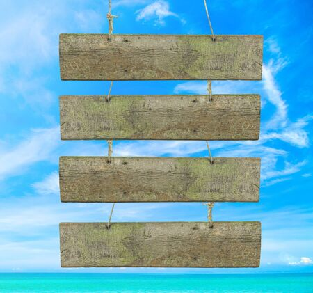 wooden insert: vintage wooden signboard with blank space for insert texts at the beautiful beach. Stock Photo
