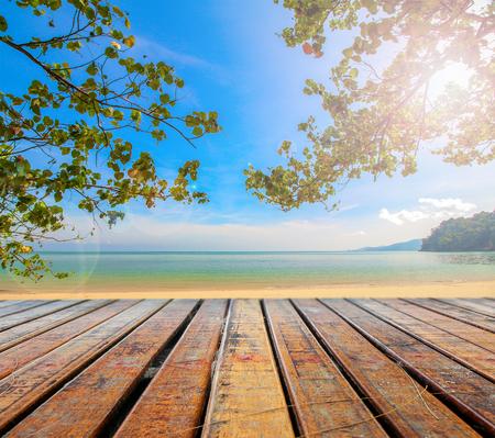 Houten plank onder foto van strand met boom om te ontspannen