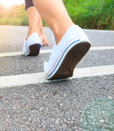 Girl starting running on the road to the nature background on morning Stock Photo