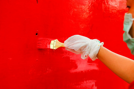 woman artist use brush with red color on wall.