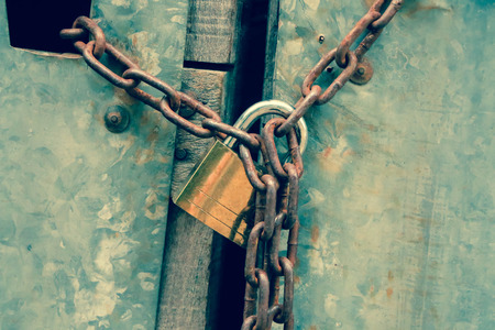 keep gate closed: Closed up key lock with a chain on an old wooden metal door