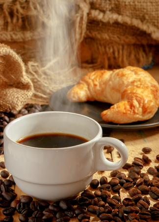 breakfast cup: Hot coffee cup and breakfast baked croissants on wooden background Stock Photo