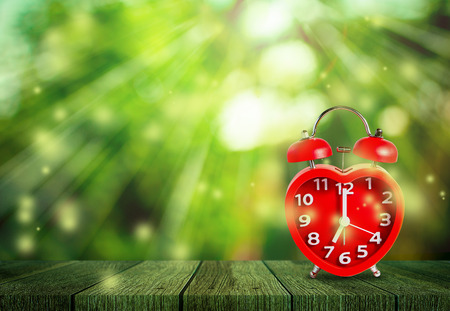 Red clock mark on 7 oclock put on wooden tabletop with abstract blurred on fresh green nature background and bokeh of sunlight ray, Time to relax concept.