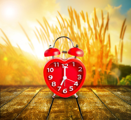 Red clock mark on 7 oclock put on wooden tabletop with abstract blurred on fresh green nature background and bokeh of sunlight ray, Time to relax concept Stock Photo
