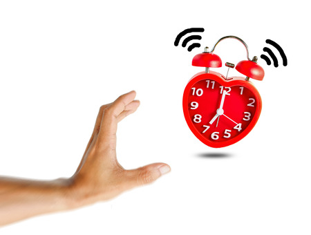 Red bell alarm clock wake up at 7 oclock with human hand try to stop it.