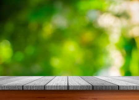 dept: Close up grunge rustic green wooden table top shallow dept of field with sunlight ray of blurred fresh green nature background for products display.