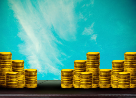 many coins with abstract blurred of sky and sunlight background, investment concepts. Stock Photo