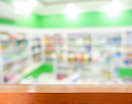 shelf: Brown wooden tabletop with blurred pharmacy or medicine shelf at the hospital
