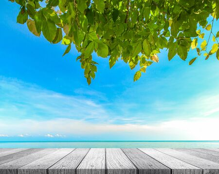 Soft white wooden tabletop with beautiful nature beach and blue sky background use for put your product or something Stock Photo